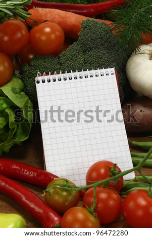 little plaid shopping list with fresh vegetables and pencil on a wooden background
