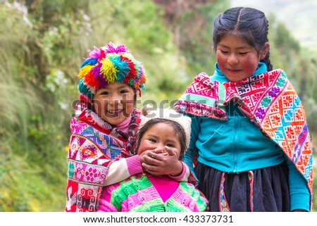 Little playful Quechua tribe girls in traditional clothing in Patacancha village in Sacred Valley, Peru. 11/APR/2016 - stock photo