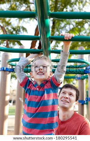 little positive boy at the monkey bars and his father watching and helping - stock photo
