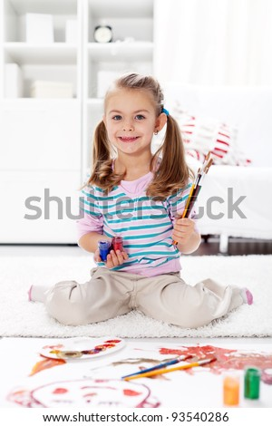 Little preschool artist girl painting at home sitting on the floor - stock photo