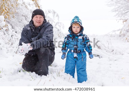 Little preschool boy and his father playing with first snow in forest
