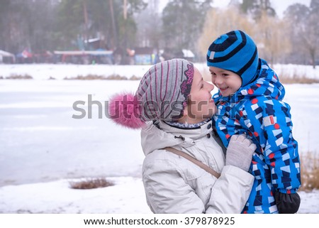 Little preschool boy and his mother playing with first snow in park. embraceing mother - stock photo