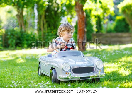 Little preschool boy driving big toy old vintage car and having fun, outdoors. Active leisure with kids on warm summer sunny day. - stock photo