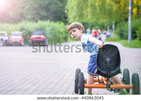Little preschool boy driving big toy sports car and having fun, outdoors. Active leisure with kids on warm summer day or evening. - stock photo