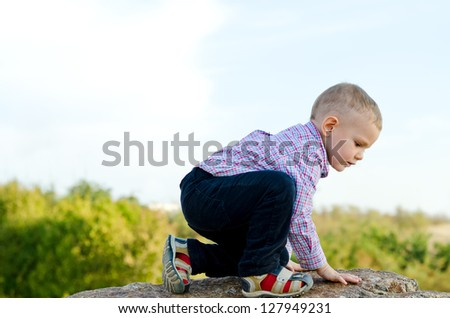 Little preschool boy exploring the countryside climbing onto a large rock, sideways view against cloudy blue sky - stock photo