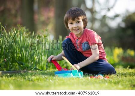 Little preschool child, boy playing with plasticine dough toy in summer garden - stock photo