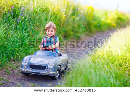 Little preschool kid boy driving big toy car and having fun with playing, outdoors. Child enjoying warm summer day in nature landscape - stock photo