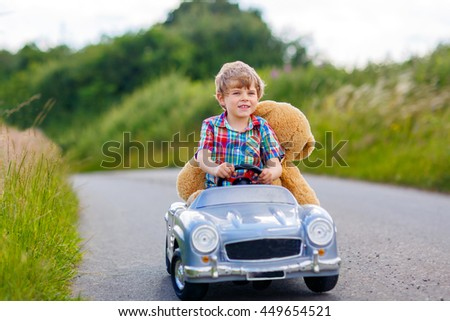 Little preschool kid boy driving big toy car and having fun with playing with his plush toy bear, outdoors. Child enjoying warm summer day in nature landscape - stock photo