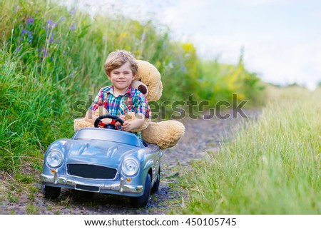 Little preschool kid boy driving big toy car and having fun with playing with his plush toy bear, outdoors. Child enjoying warm summer day in nature landscape