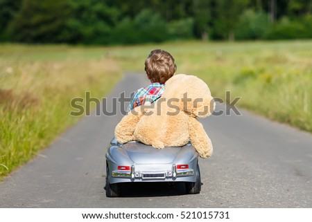 little preschool kid boy driving big toy car and having fun with playing with his plush