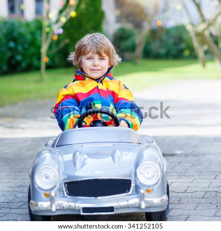 Little preschool kid boy driving big toy old vintage car and having fun, outdoors. Active leisure with kids outdoors  on warm spring or autumn day. - stock photo
