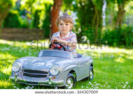 Little preschool kid boy driving big toy old vintage car and having fun, outdoors. Active leisure with children during school holidays on warm summer sunny day. - stock photo