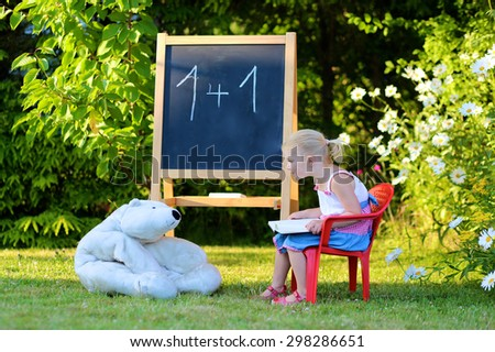 Little preschooler girl excited to go back to school. Cute toddler playing teacher role game outdoors. Happy kid reading book, leaning letters and numbers at kindergarten. Children education concept.  - stock photo