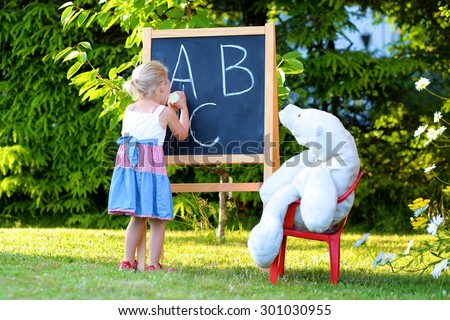 Little preschooler girl excited to go back to school. Cute toddler playing teacher role game outdoors. Happy kid leaning letters at kindergarten. Children education concept.  - stock photo