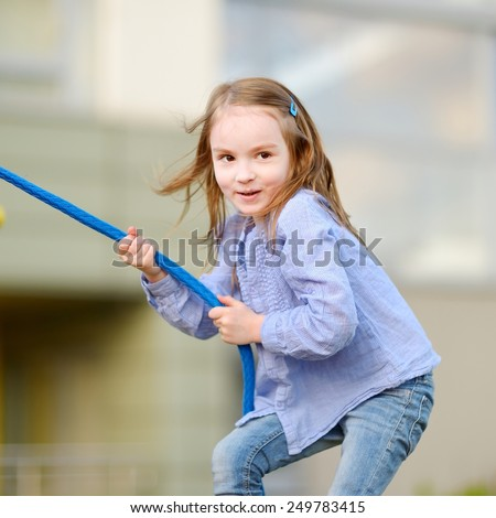 Little preschooler girl having fun with a rope at a playground - stock photo