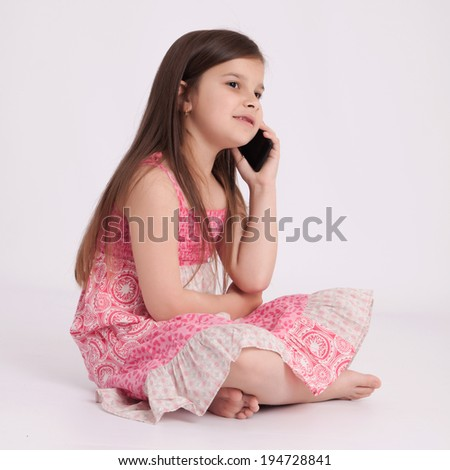 Little preschooler girl in a pink dress holding a mobile phone - stock photo