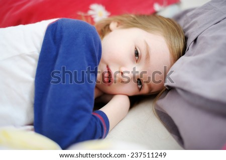 Little preschooler girl in bed on sunny morning - stock photo