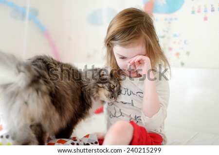 Little preschooler girl in pajamas and her cat on sunny morning - stock photo