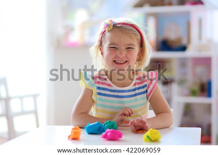 Little preschooler girl playing with plasticine. Happy child, adorable creative toddler playing with colorful modeling compound, sitting at white table in bright sunny room at home or kindergarten - stock photo
