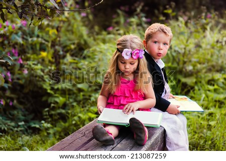 Little preschooler kid reading outdoor - stock photo