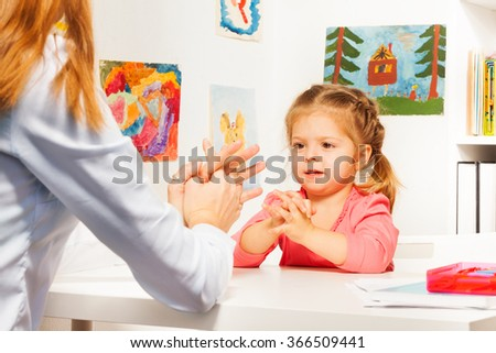 Little preschooler with her teacher at the table - stock photo