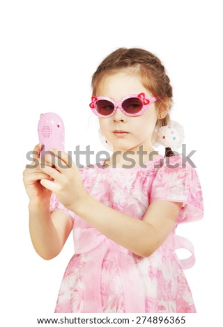 Little pretty girl in beautiful pink dress with toy mobile - stock photo