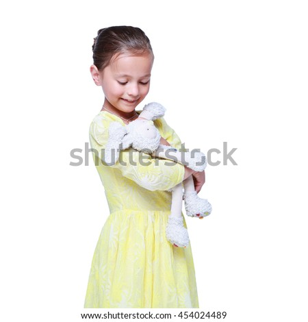 Little pretty girl in yellow dress hugs her toy rabbit and smiles. happy child plays with toy hare isolated on white - stock photo