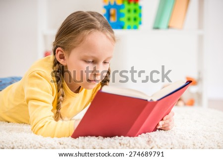 Little pretty  girl in yellow  pullover reading book on colorful background.