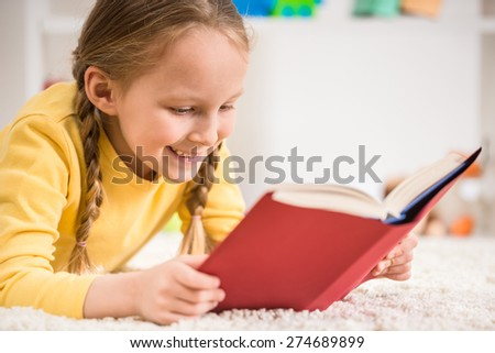 Little pretty  girl in yellow  pullover reading book on colorful background. - stock photo