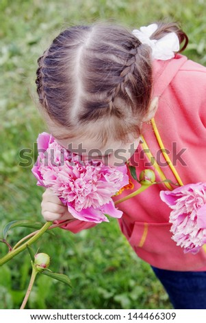 Little pretty girl inhales the scent of a big pink flower - stock photo