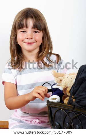 Little pretty girl pushing a doll buggy - stock photo