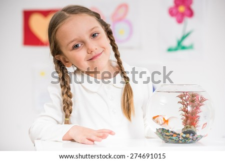 Little pretty  smiling girl in white  pullover  playing with gold fish in aquarium on colorful background.