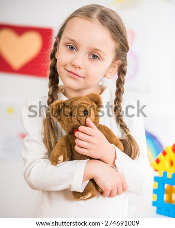 Little pretty  smiling girl in white  pullover with teddy on colorful background. - stock photo