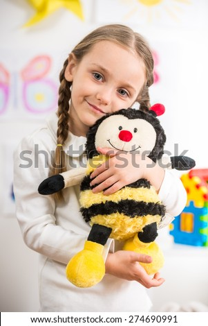 Little pretty  smiling girl in white  pullover with toy bee on colorful background. - stock photo