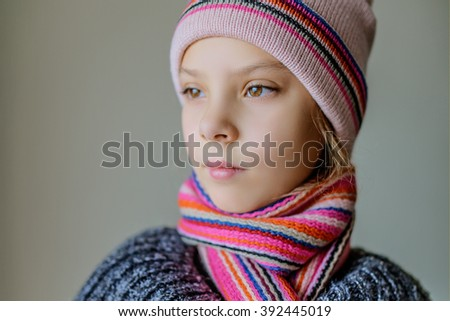 Little pretty thoughtful girl in a cap and a scarf closeup. - stock photo