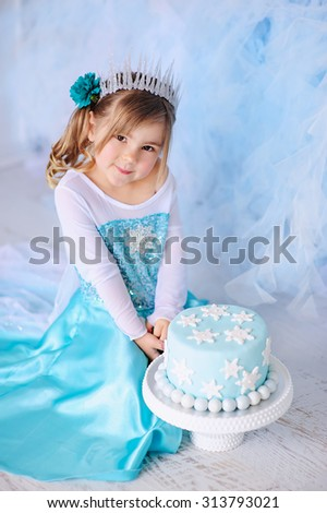Little princess girl on a styled Frozen birthday party with snowflakes cakes - stock photo