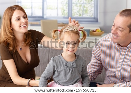 Little princess in tiara smiling, pregnant mother and father adoring. - stock photo