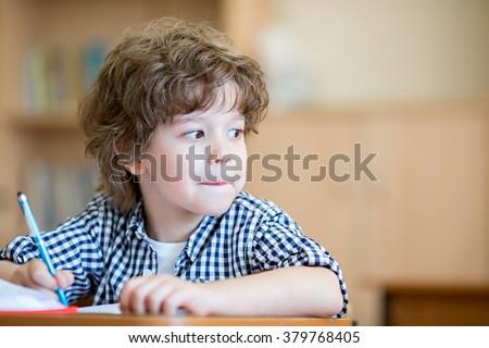 Little pupil at desk - stock photo