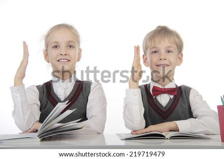 little pupils sitting at a desk and pull arm - stock photo