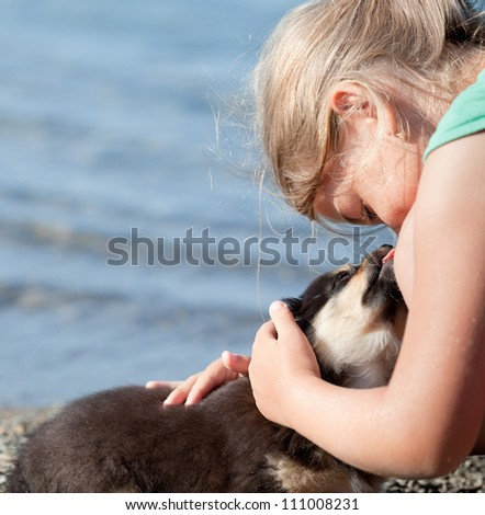 Little puppy licks the nose of a nine-year-old girl. Close up - stock photo