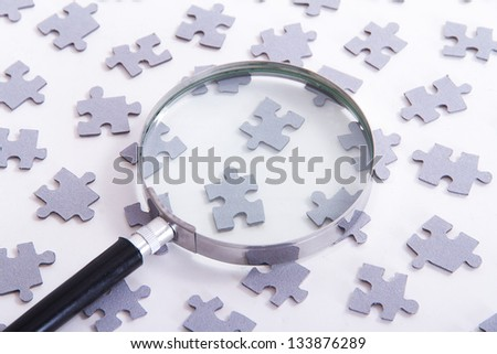 Little puzzle pieces and magnifying glass, isolated on white background. - stock photo