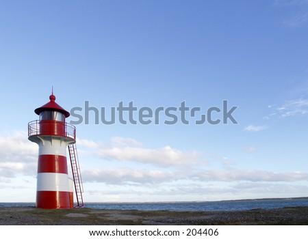 Little red and white striped lighthouse, Limfjorden, Denmark - stock photo