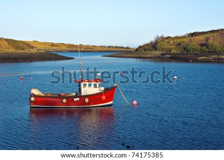 Little red fishing boat lies peacefully at anchor in a sheltered bay on a calm early Spring evening. - stock photo