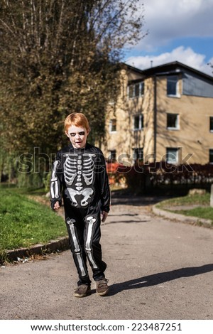 little red haired boy wearing halloween skeleton costume. Outdoor portrait - stock photo