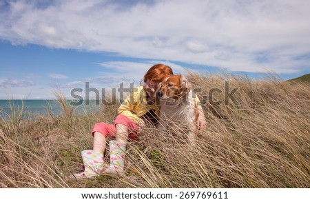 little red haired girl playing with her pet dog in dune grasses on a sunny day  - stock photo