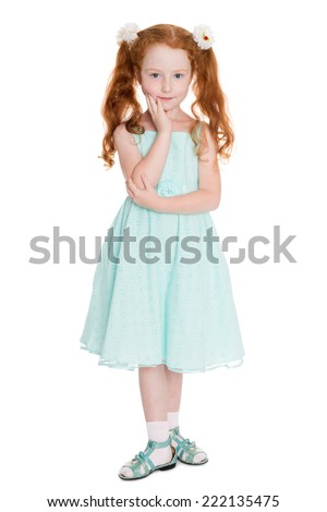 Little red haired girl standing in a pensive pose, six years.  - stock photo