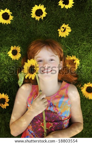 little red headed girl with sunflowers laying on grass