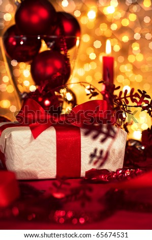 Little red ribboned gift with a sprig of holly on plate - stock photo