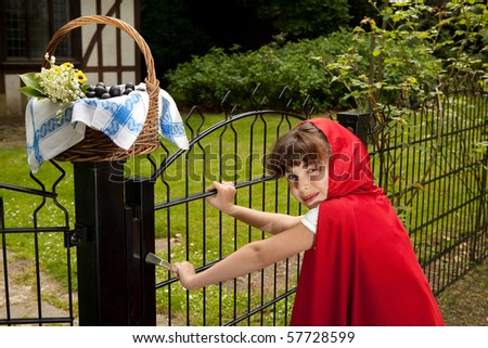 Little red riding hood arriving at the gate of her grandmother's cottage