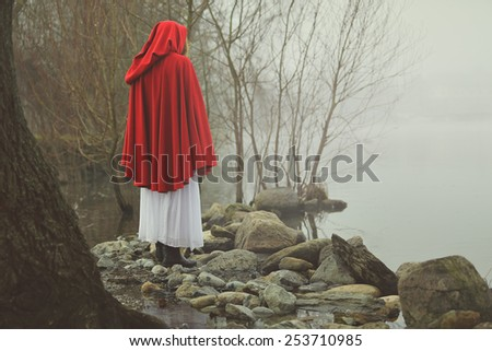 Little red riding hood on a shore of a misty lake . Sadness and surreal concept   - stock photo